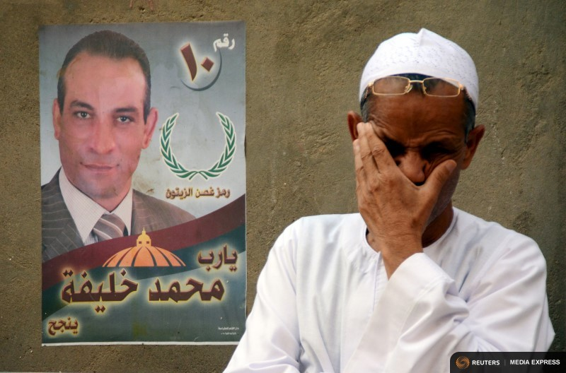 A man is seen near an election poster for parliamentary candidate Mohamed Khalifa at a village in Minya governorate, south of Cairo, Egypt, October 8, 2015. REUTERS/Stringer